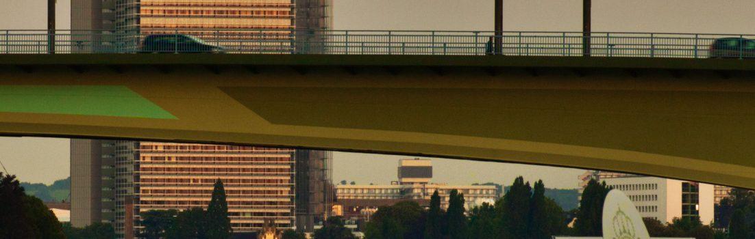 Sicht über den Rhein bei Sonnenuntergang mit UNO und DHL und Kennedy-Brücke